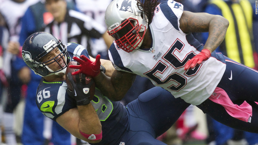 Zach Miller of the Seattle Seahawks pulls in a pass while being defended by Brandon Spikes of the New England Patriots.