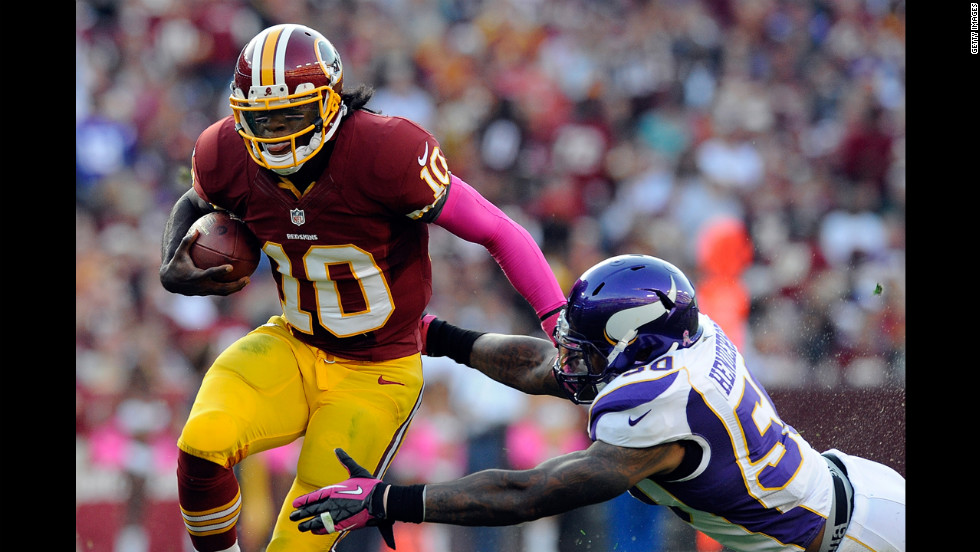 Quarterback Robert Griffin III of the Washington Redskins is tackled by Erin Henderson of the Minnesota Vikings on Sunday at FedExField in Landover, Maryland.