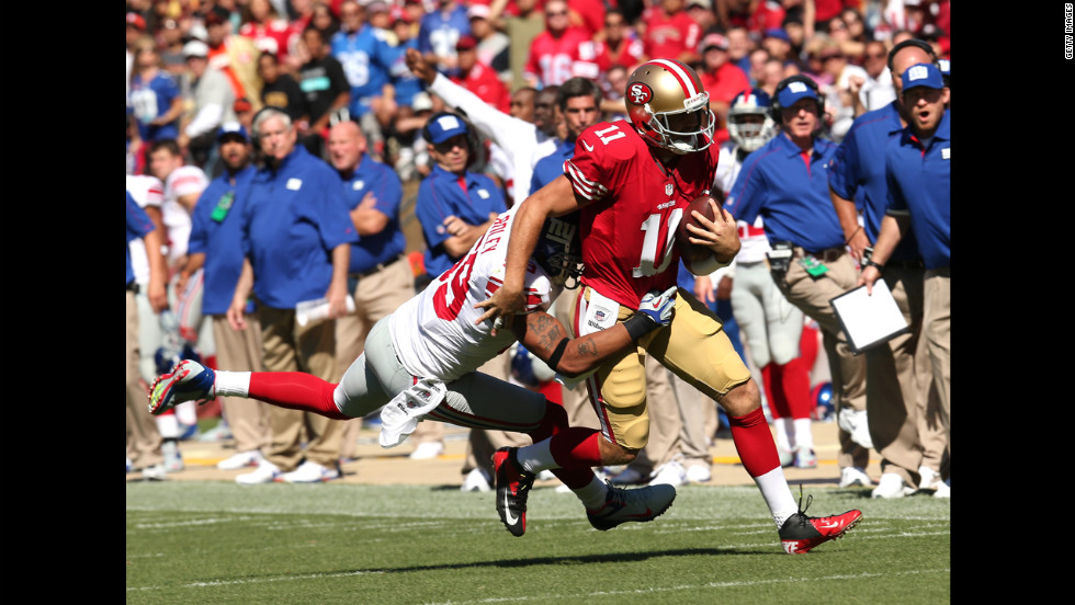 San Francisco 49ers quarterback Alex Smith runs the ball for a gain as Michael Boley of the New York Giants makes the tackle.
