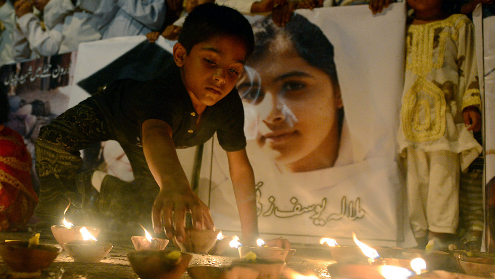 A Pakistani youth places an oil lamp next to a photograph of teen activist Malala Yousufzai on Friday, October 12, 2012, in Karachi, Pakistan.