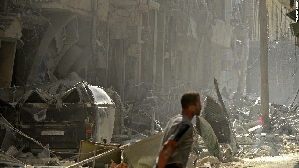 A Syrian man walks past destroyed buildings following shelling by regime forces in Aleppo on Monday, October 15.