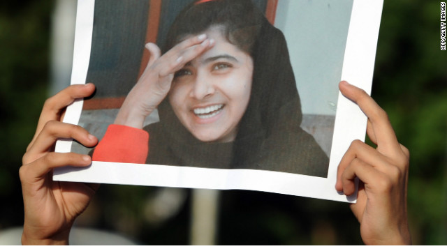 A Pakistani female activist of an Islamic Minhaj-ul-Quran Party holds a photograph of child activist Malala Yousafzai during a protest against the assassination attempt by Taliban, in Islamabad on October 13, 2012. A Pakistani schoolgirl shot in the head by the Taliban remained on a ventilator in hospital Saturday, as people continued to pray for her recovery, the military said.