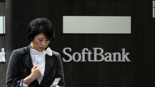 A pedestrian uses her mobile phone before a Softbank mobile phone shop in Tokyo on October 12, 2012. Japanese mobile carrier Softbank is eyeing a monster 25 billion USD buy-in to the US telecom market including the takeover of Sprint Nextel in what could be among Japan Inc.'s biggest-ever overseas deals. Sprint Nextel confirmed it was talking with Softbank about a takeover, which could help vault the Japanese firm into the top three mobile giants globally. AFP PHOTO / Yoshikazu TSUNO (Photo credit should read YOSHIKAZU TSUNO/AFP/GettyImages)