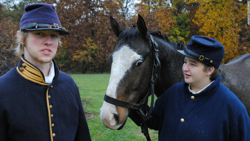 Not just a generational thing: Two teenage re-enactors watch their horse on the battleground