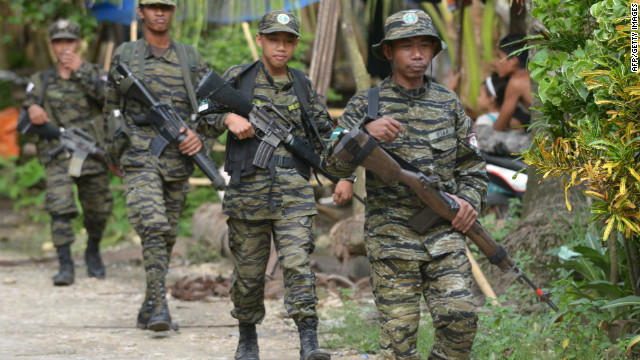 Muslim fighters patrol the camp of the Moro Islamic Liberation Front in the southern Philippines on Wednesday.