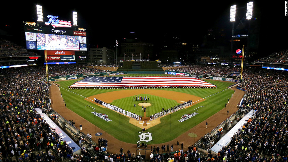 An American flag is spread across the field as players from the Detroit Tigers and the New York Yankees line up for the national anthem prior to the start of the game.