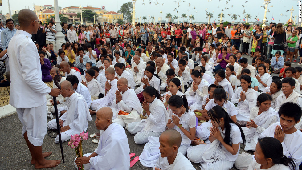 Cambodian nuns and other people gather in front of the palace on Monday, October 15.