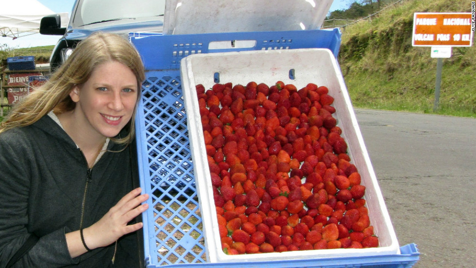 "Elyse Pasquale poses with fresh strawberries in the shadow of the Poas Volcano, Costa Rica. ""Food is an entirely sensory experience. You can touch it, you can smell it, you can taste it. What better way is there to learn about a place you've never been before,"" she asks."