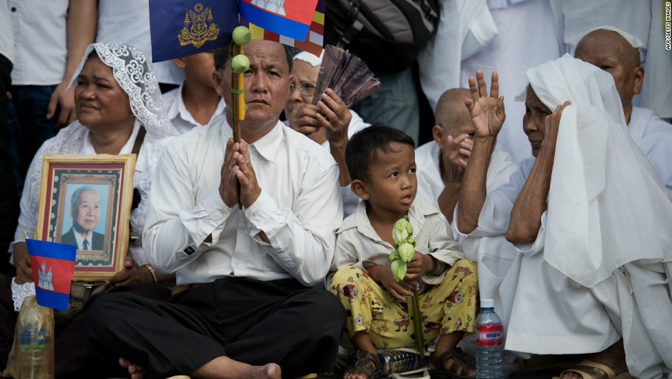Cambodian mourners hold pictures of late King Norodom Sihanouk and national flags in front of the Royal Palace in Phnom Penh.