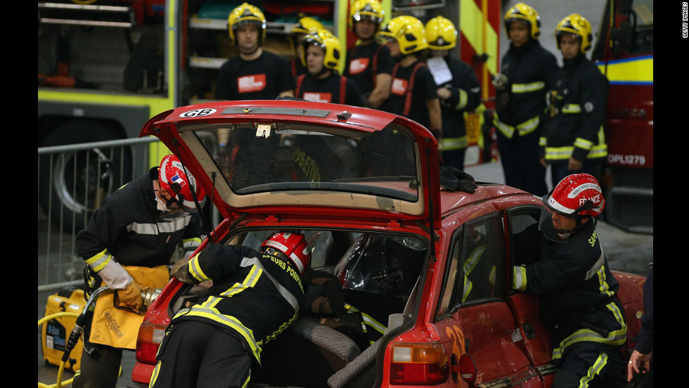 Members of the Fire Brigade reach into a car during a extrication and trauma challenge.