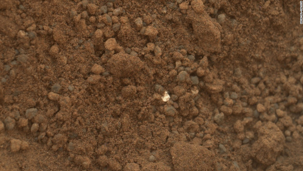This image shows part of the small pit or bite created when NASA's Mars rover Curiosity collected its second scoop of Martian soil on October 15, 2012. The rover team determined that the bright particle near the center of the image was native to Mars, and not debris from the rover's landing.