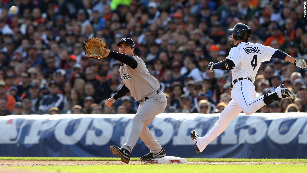 Mark Teixeira of the New York Yankees stretches for the ball as Infante beats the throw to reach first safely.