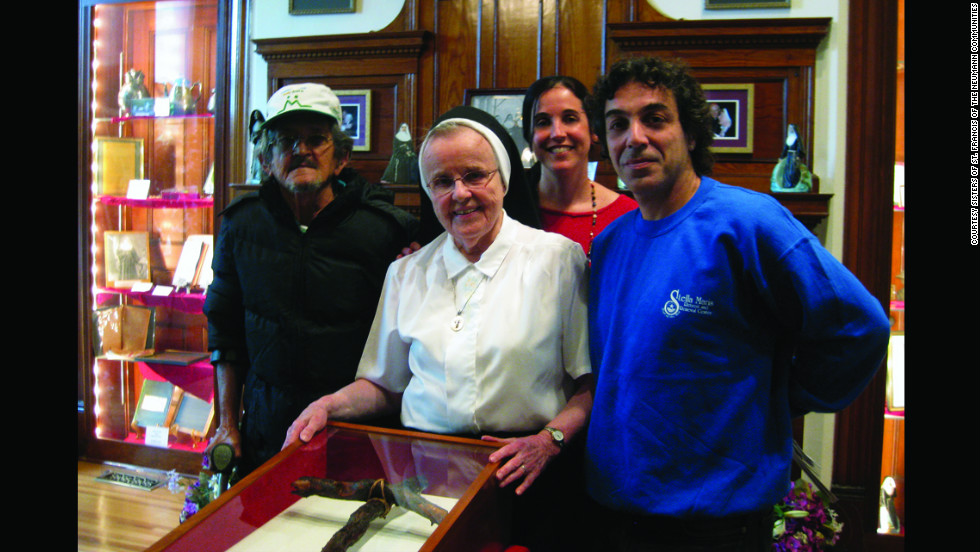 Sister Mary Christopher Dixon, OSF, shows a relic of branches found at Mother Marianne's burial site in Kaluapapa to Brazilian representatives from the International Association for Integration Dignity and Economic advancement, or IDEA.  The relics are at the Shrine and Museum of Saint Marianne Cope in Syracuse, New York.