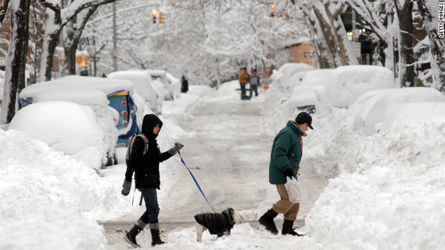 A woman walking a dog and a man cross a snow covered street on January 27, 2011 in Brooklyn, New York.