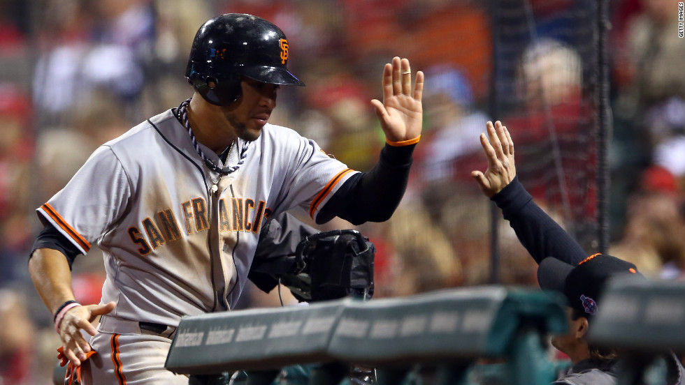 No. 7 Gregor Blanco of the Giants is congratulated at the dugout after scoring in the fourth inning against the Cardinals.