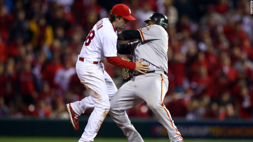 No. 48 Pablo Sandoval of the Giants crashes into No. 38 Pete Kozma of the Cardinals after No. 31 pitcher Lance Lynn of the Cardinals has a throwing error allowing No. 19 Marco Scutaro of the Giants to score in the fourth inning.