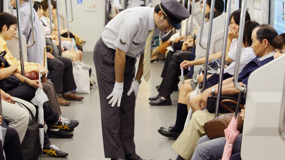 "A station staff member bows his head in front of passengers to apologize for delayed train at Japan Railway's station in Saitama city, northern Tokyo. The rail and subway network runs very smoothly, says Barron. ""Compared to New York, [Tokyo] is really efficient, really orderly, really clean ... """