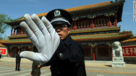 Chinese policeman blocks photos being taken outside Zhongnanhai which serves as the central headquarters for the Communist Party of China after the sacking of politician Bo Xilai in Beijing on April 11, 2012.