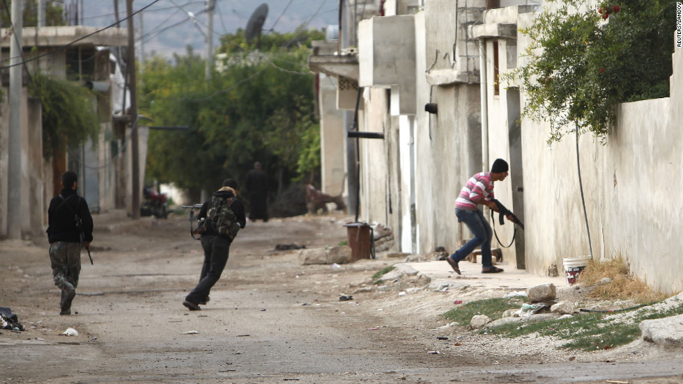 A member of the Free Syrian Army flees sniper shots from pro-government forces in Salqin, Syria, on Monday, October 22.