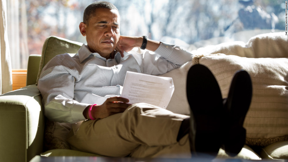 Obama reads briefing material while meeting with advisers inside his cabin on Sunday, October 21, at Camp David, Maryland.