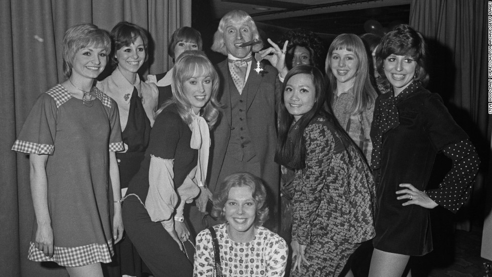 "Savile shows off his Order of the British Empire to members of the ""Second Generation"" song and dance troupe."