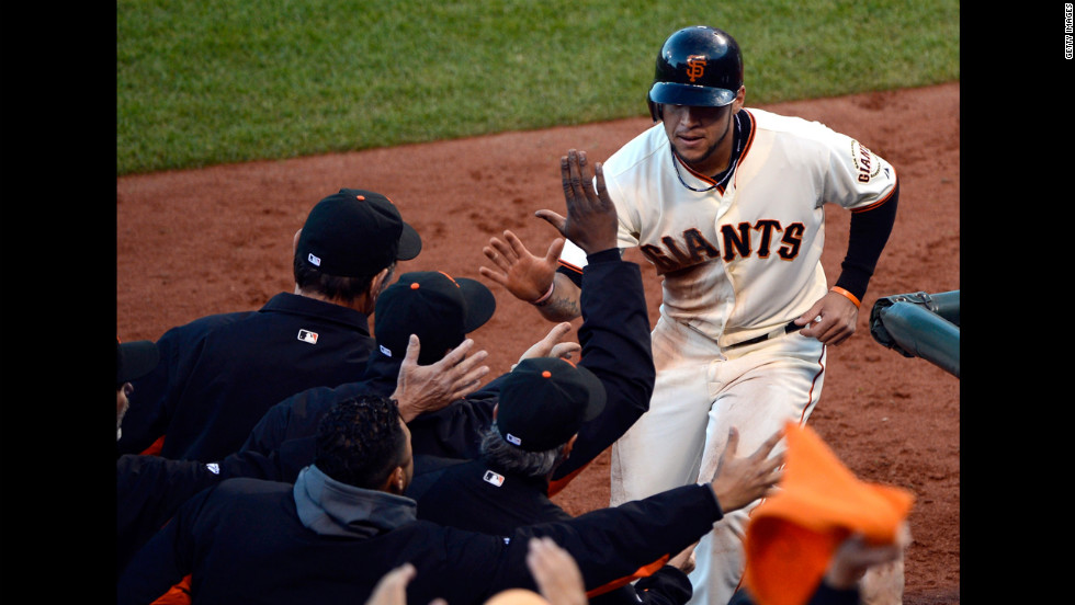 No. 7 Gregor Blanco of the Giants is congratulated by manager Bruce Bochy after Blanco scores on a base hit by No. 18 Matt Cain in the second inning.