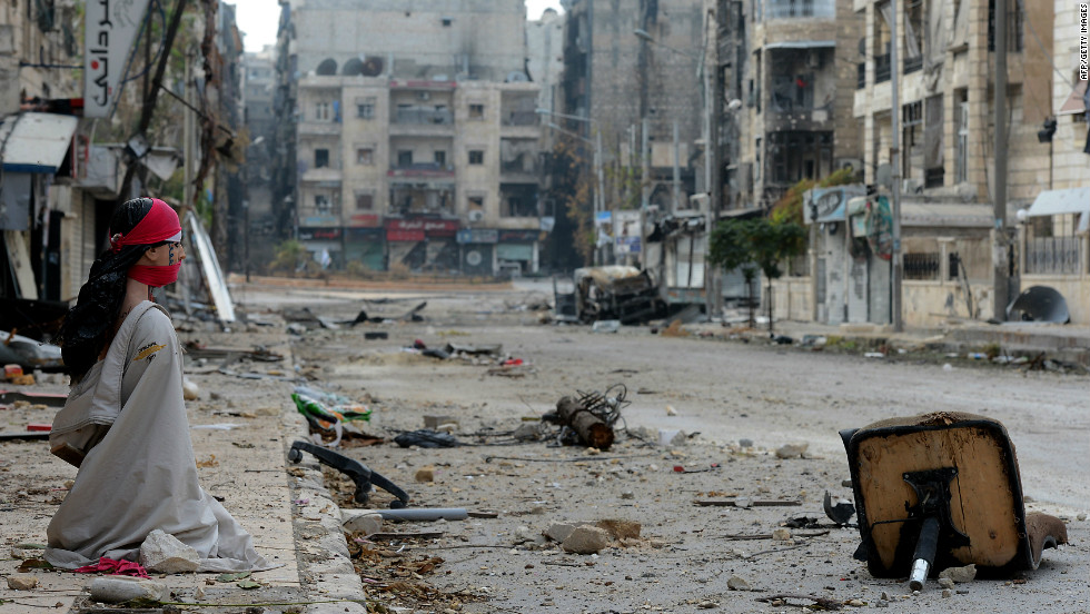 A woman sits on the sidewalk of a debris strewn street in Aleppo, Syria, on October 23.