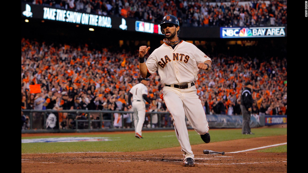 Angel Pagan of the San Francisco Giants scores a run from a hit by Marco Scutaro.