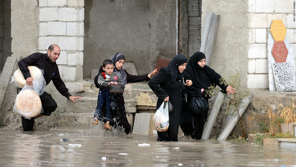 A family crosses a street flooded by heavy rains in Aleppo, Syria, on Thursday.
