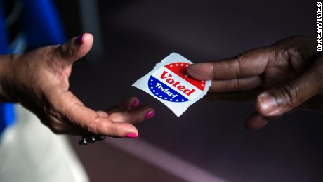 "A poll worker hands out ""I Voted Today"" stickers during the first day of early voting October 22, 2012 in Washington, DC. Citizens of the District of Columbia began early voting today for the November 6th elections which will include the 2012 US Presidential election.  AFP PHOTO/Brendan SMIALOWSKI        (Photo credit should read BRENDAN SMIALOWSKI/AFP/Getty Images)"