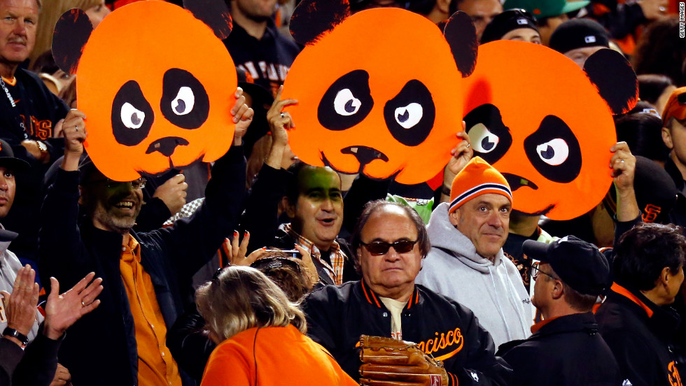 Fans hold up cutout faces of pandas in support of Pablo Sandoval of the San Francisco Giants.