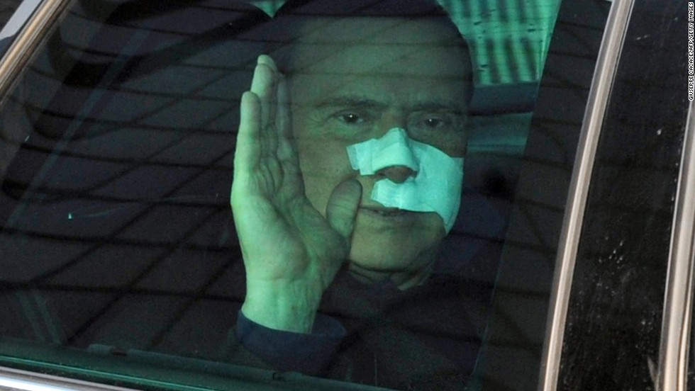 Berlusconi waves to journalists as he leaves San Raffaele hospital in Milan on December 17, 2009. Berlusconi suffered severe facial wounds in a violent attack.