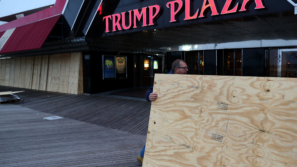 Scott Davenport brings plywood to cover the windows at the Trump Plaza casino on the boardwalk in Atlantic City, New Jersey, on Sunday.