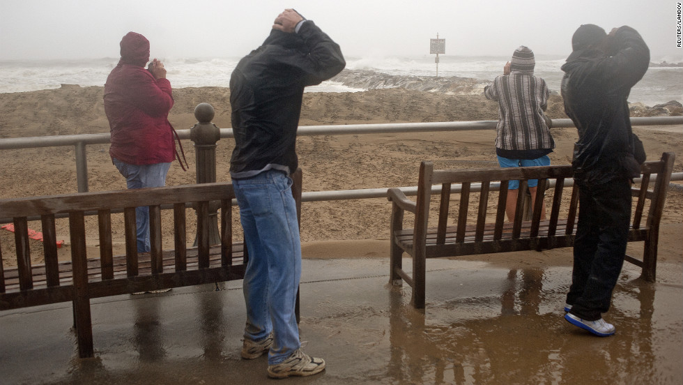 People look at the surf as high winds and heavy rain from Hurricane Sandy arrive in Virginia Beach, Virginia, on Sunday.