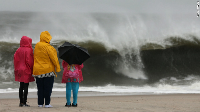 People stand on the beach watching the heavy surf caused by the approaching Hurricane Sandy, on Sunday, October 28, in Cape May, New Jersey. Hurricane Sandy is expected to hit the New Jersey coastline sometime on Monday bringing heavy winds and floodwaters.