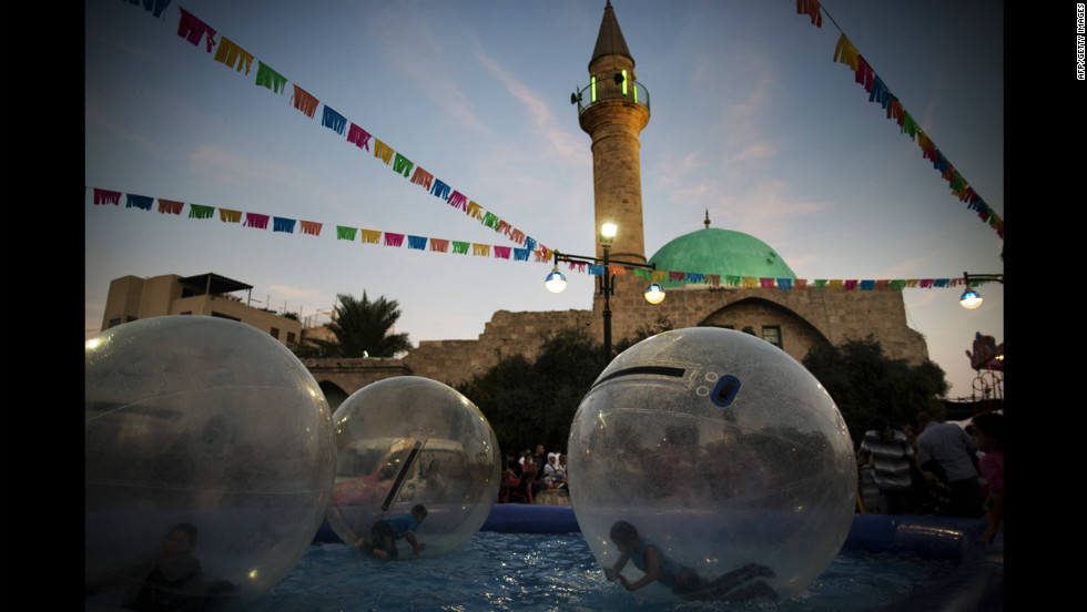 Arab Israeli children roll inside air balls floating on a pool at an amusement park on Saturday in the northern Israeli city of Acre.