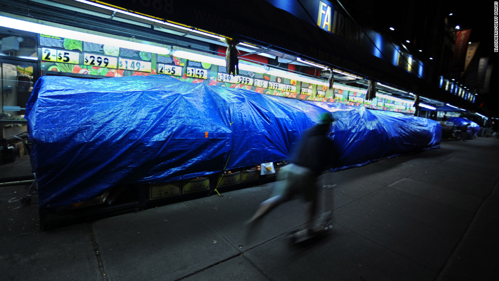 A pedestrian rides past fruit and vegetable stalls covered with tarps on Broadway on October 28.