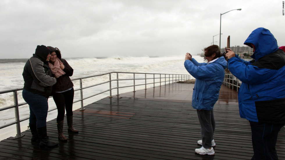 People pose for pictures on the Rockaway Beach Boulevard in Queens ahead of the storm on October 29.