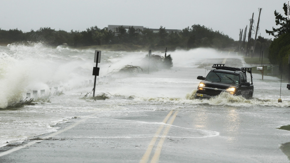 A truck fights its way through water on a road in Southampton, New York, on Monday.
