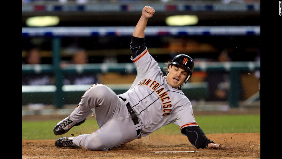 Ryan Theriot of the Giants slides to home in the tenth inning.