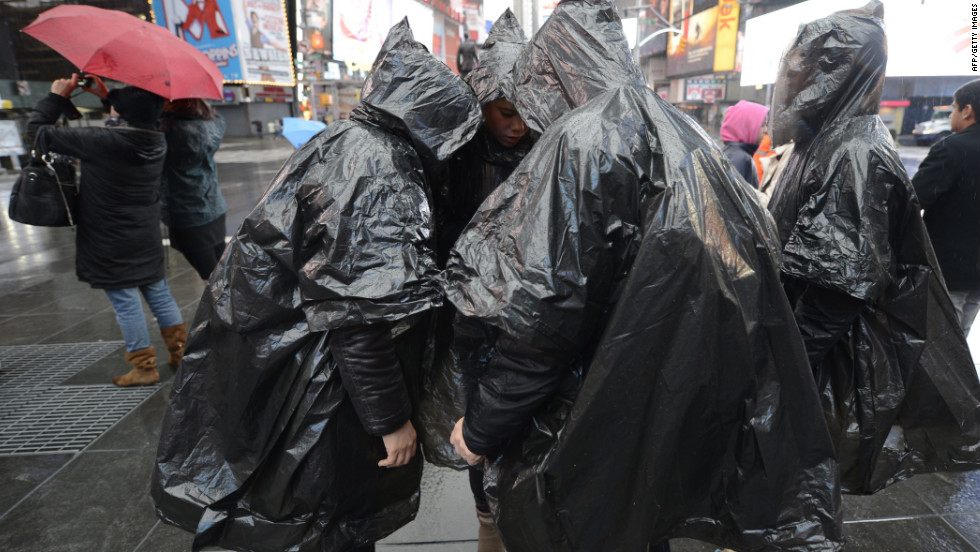 Tourists wear plastic ponchos in Times Square on Monday.