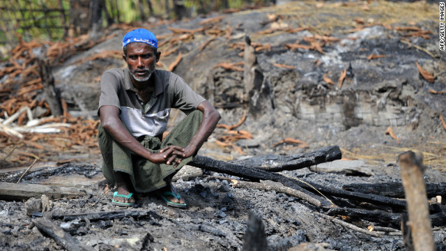 A Muslim Rohingya man sits at his burnt home at a villaged in Minpyar in Rakhine state in October.