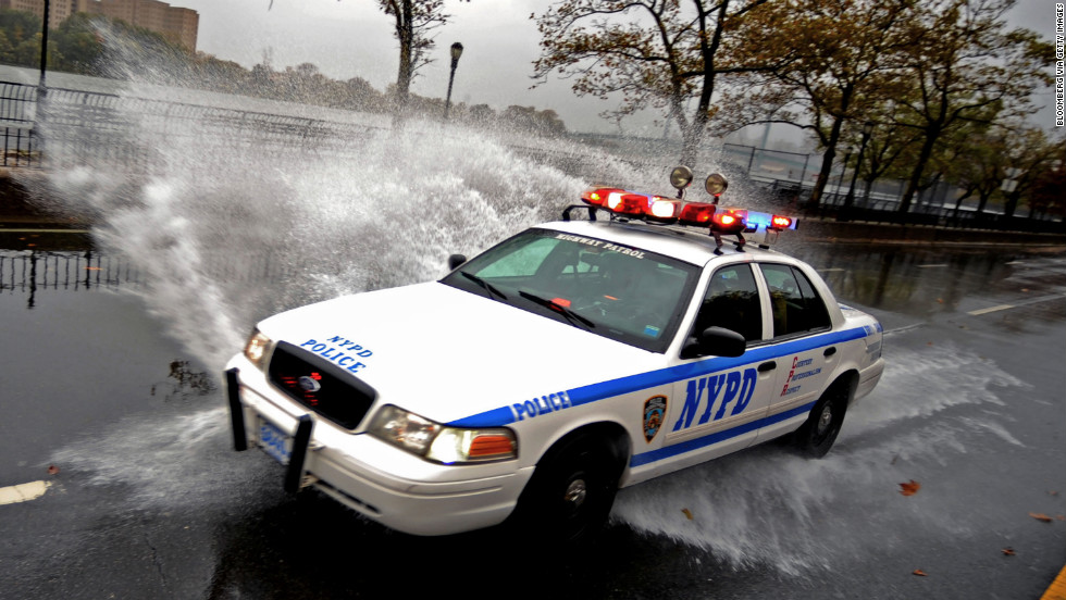 A police vehicle drives through a flooded area in New York on Monday.