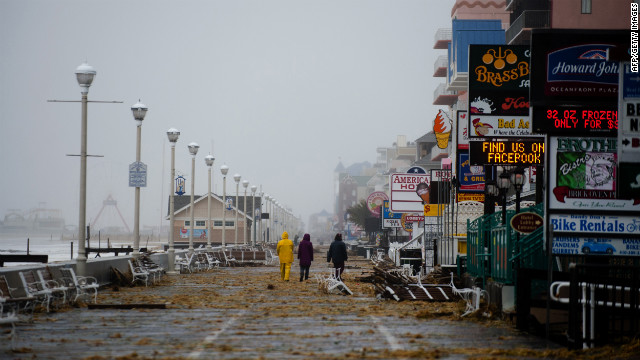 People walk on the boardwalk in Ocean City, Maryland, on October 29, 2012 as Hurricane Sandy nears landfall in the area.      AFP PHOTO/Jim WATSON        (Photo credit should read JIM WATSON/AFP/Getty Images)