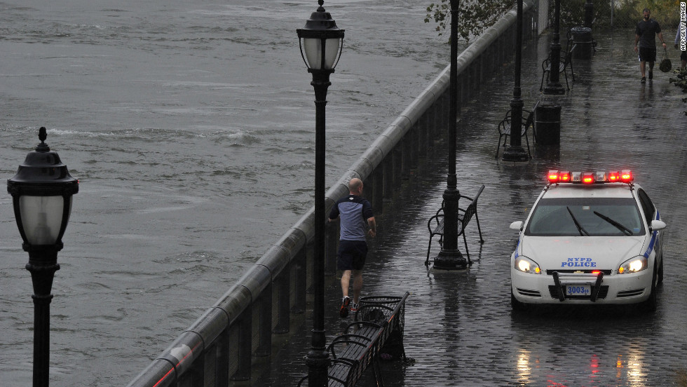 A jogger runs along the East River in New York on Monday as a police car secures the area.