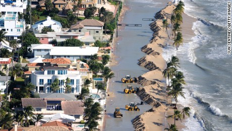 Work crews push sand from a roadway in Fort Lauderdale, Florida, due to storm surge related flooding on October 29.