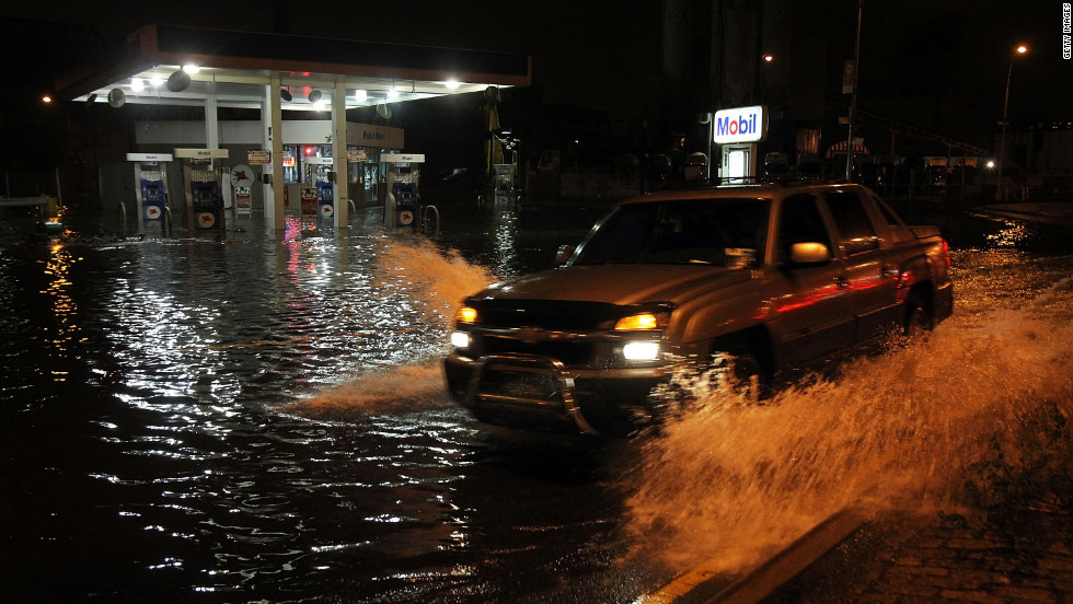 A truck drives by a flooded gas station in the Gowanus section of Brooklyn on Monday.