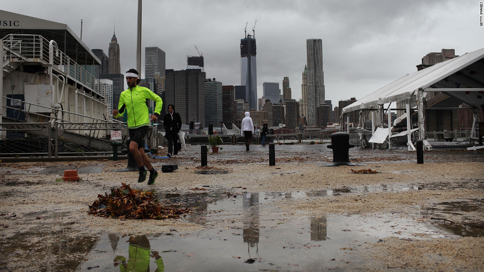 A man jogs near a darkened Manhattan skyline on Tuesday after much of New York City lost electricity.