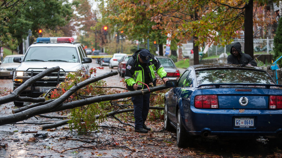 A police officer helps remove a tree branch brought down during the storm in Washington on Tuesday.
