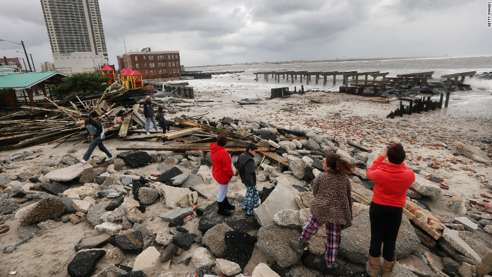 People stand among the debris of the destroyed section of Atlantic City, New Jersey's, uptown boardwalk on Tuesday.